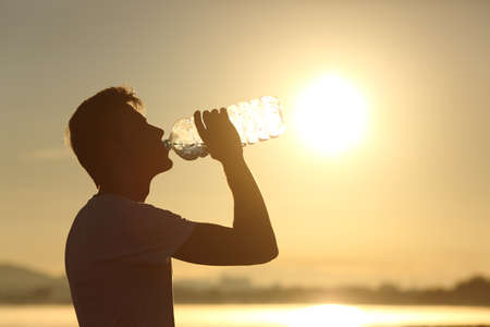 Photo pour Profile of a fitness man silhouette drinking water from a bottle at sunset with the sun in the background - image libre de droit