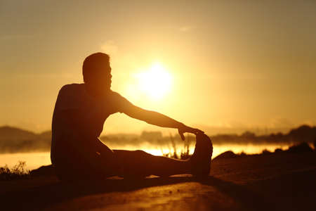 Photo pour Silhouette of a fitness runner man stretching at sunset with the sun in the background - image libre de droit