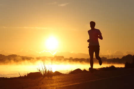 Photo pour Silhouette of a man running at sunrise with the sun in the background - image libre de droit