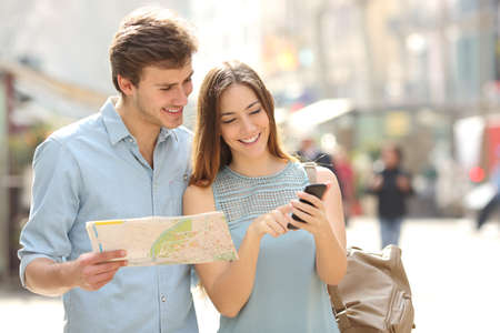 Foto de Couple of tourists consulting a city guide and smartphone gps in the street searching locations - Imagen libre de derechos