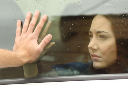 Photo for Couple saying goodbye before car travel holding hands through the window - Royalty Free Image