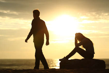Photo pour Couple silhouette breaking up a relation on the beach at sunset - image libre de droit