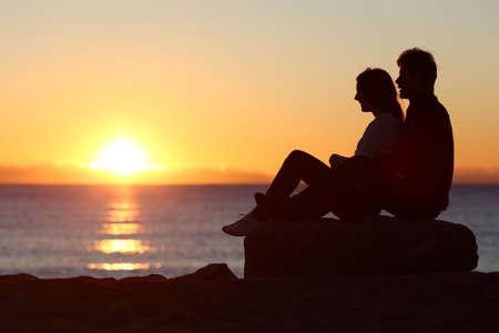Foto de Side view of a couple silhouette sitting watching sun at sunset on the beach - Imagen libre de derechos