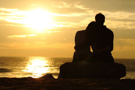 Photo pour Couple silhouette cuddling and watching sun at sunset on the beach - image libre de droit