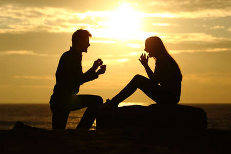 Proposal on the beach with a man silhouette asking for marry at sunset with the sun in the background