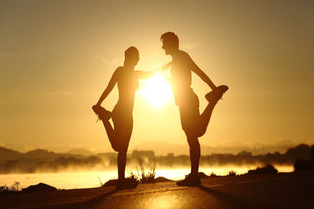 Photo for Silhouette of a fitness couple profile stretching at sunset with the sun in the background - Royalty Free Image