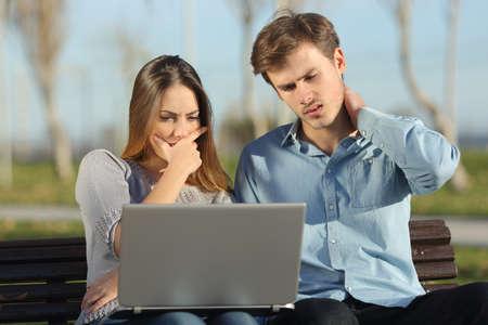 Photo pour Worried students or entrepreneurs watching a laptop sitting on a bench in a park - image libre de droit