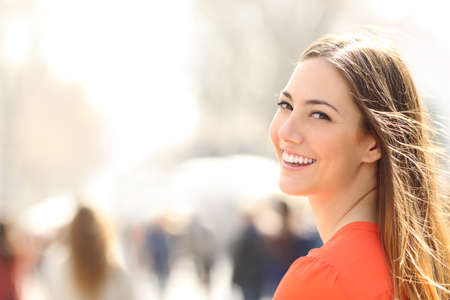 Photo for Beauty woman with perfect smile and white teeth walking on the street and looking at camera - Royalty Free Image