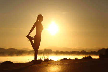 Photo for Silhouette of a fitness woman profile stretching at sunrise with the sun in the background - Royalty Free Image