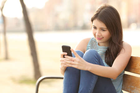 Photo pour Teen girl using a smart phone and texting sitting in a bench of an urban park - image libre de droit