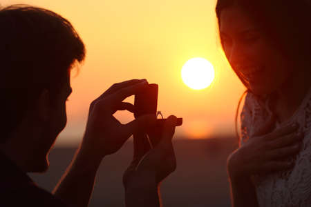 Photo for Back light of a couple proposal of marriage on the beach at sunset - Royalty Free Image