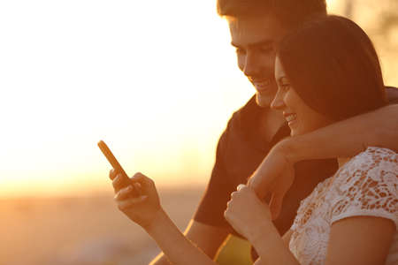 Photo pour Happy couple using a smartphone in a sunset back light on the beach - image libre de droit