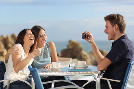 Photo for Friends on vacations laughing and taking photo with a smart phone in a restaurant on the beach - Royalty Free Image