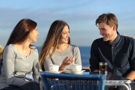 Photo for Friends talking in a restaurant terrace on the beach in a sunny day - Royalty Free Image
