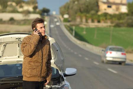 Foto de Happy man calling roadside assistance for his breakdown car in a country road - Imagen libre de derechos