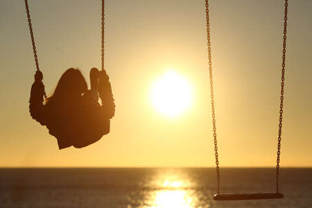Foto de Back light of a lonely woman silhouette swinging at sunset on the beach with another empty swing - Imagen libre de derechos