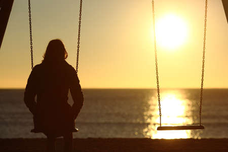 Photo pour Lonely woman watching sunset alone in winter on the beach at sunset - image libre de droit