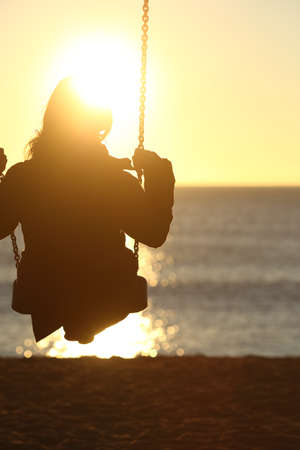 Photo for Woman silhouette swinging at sunset on the beach and watching the sun - Royalty Free Image