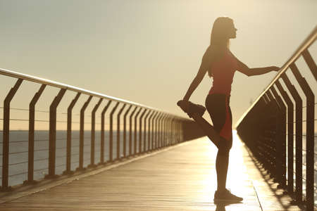 Photo for Woman silhouette exercising stretching on a bridge after running at sunset - Royalty Free Image