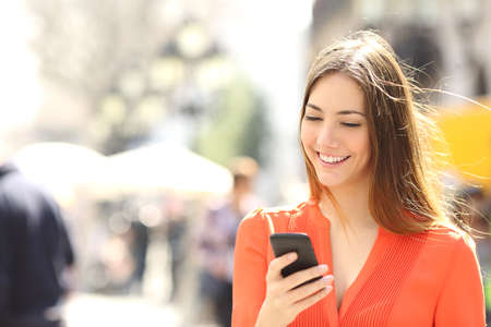 Foto de Woman wearing orange shirt texting on the smart phone walking in the street in a sunny day - Imagen libre de derechos