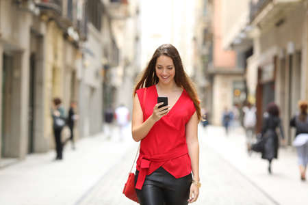 Foto de Front view of a fashion happy woman walking and using a smart phone on a city street - Imagen libre de derechos