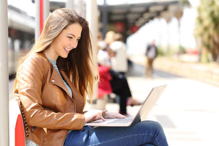 Photo for Side view of a girl using a laptop while waiting in a train station in a sunny day - Royalty Free Image