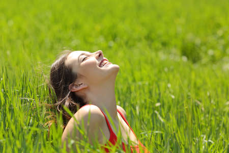 Photo pour Happy girl face breathing fresh air and enjoying the sun in a meadow in a summer sunny day - image libre de droit