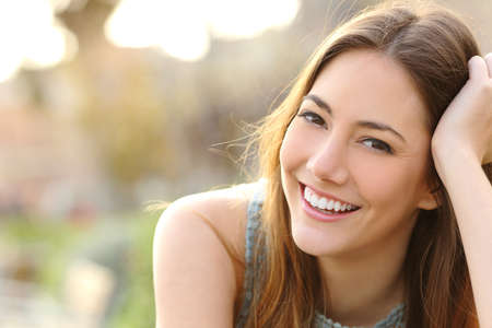 Foto de Woman smiling with perfect smile and white teeth in a park and looking at camera - Imagen libre de derechos
