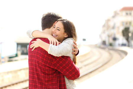 Foto de Happy couple hugging in a train station after arrival - Imagen libre de derechos