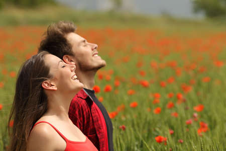 Foto de Happy couple breathing fresh air in a colorful field with red poppy flowers - Imagen libre de derechos