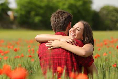 Photo pour Happy couple hugging affectionate after proposal in a green field with red flowers - image libre de droit