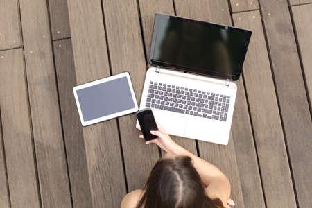 Foto de Woman using multiple devices phone laptop and tablet lying in a wood bench in a park - Imagen libre de derechos