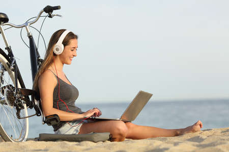 Photo for Teen girl studying with a laptop on the beach leaning on a bicycle - Royalty Free Image