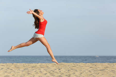 Foto de Side view, of a teen girl wearing red shirt and shorts jumping happy on the beach - Imagen libre de derechos