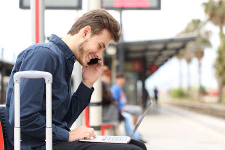 Photo pour Freelancer working with a laptop and phone in a train station while is waiting for transport - image libre de droit