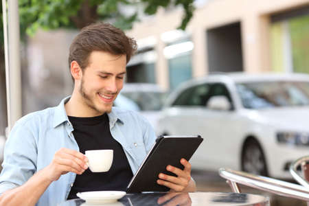 Foto de Happy man reading an ebook or tablet in a coffee shop terrace holding a cup of tea - Imagen libre de derechos