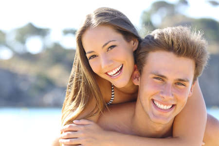 Photo pour Happy couple with perfect smile and white teeth posing on the beach looking at camera - image libre de droit