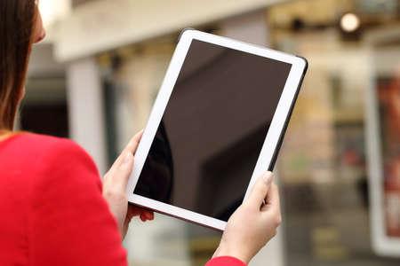 Foto de Woman using and showing a blank tablet screen in the street in front a store - Imagen libre de derechos