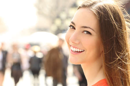 Photo for Woman face smile with perfect teeth and smooth skin looking you on the street - Royalty Free Image