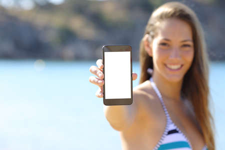 Photo pour Sunbather woman wearing bikini showing blank phone screen on the beach in summer vacations - image libre de droit