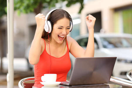 Photo for Winner girl euphoric watching a laptop in a coffee shop wearing a red shirt - Royalty Free Image