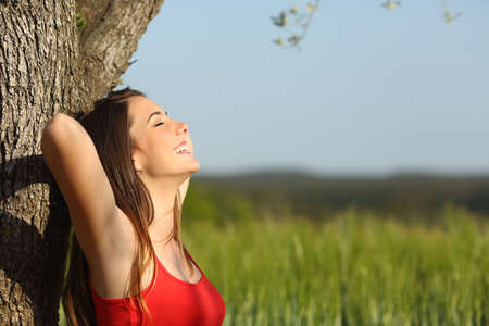 Photo pour Woman resting and relaxed comfortable leaning in a tree in a meadow in summertime - image libre de droit