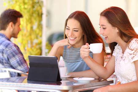 Foto de Two friends or sisters watching videos in a tablet in a coffee shop terrace - Imagen libre de derechos