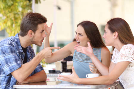 Photo for Discussion of three angry friends arguing in a coffee shop - Royalty Free Image