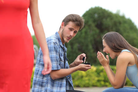 Foto de Cheater man cheating during a marriage proposal with his innocent girlfriend - Imagen libre de derechos