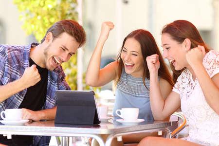 Foto de Euphoric winner friends using a tablet in a coffee shop terrace - Imagen libre de derechos