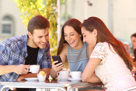 Photo pour Three happy friends watching social media in a smart phone in a coffee shop - image libre de droit