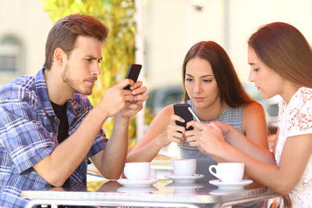 Photo pour Group of three smart phone addicted friends in a coffee shop terrace everyone with one cellphone - image libre de droit