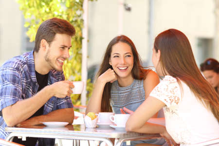 Foto de Three happy friends talking and laughing in a coffee shop terrace - Imagen libre de derechos