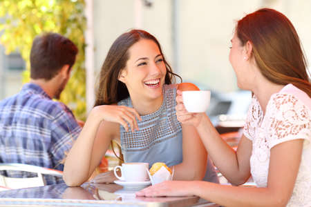 Foto de Two friends or sisters talking taking a conversation in a coffee shop terrace looking each other - Imagen libre de derechos